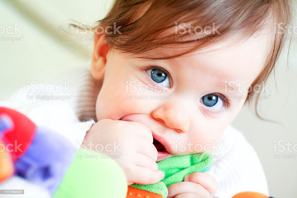A blue-eyed toddler discovering their toy stock photo