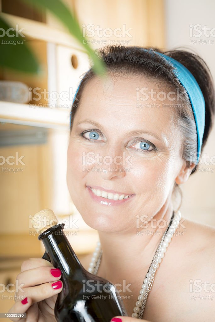 Blue-eyed Woman with Olive Oil Bottle in Kitchen royalty-free stock photo