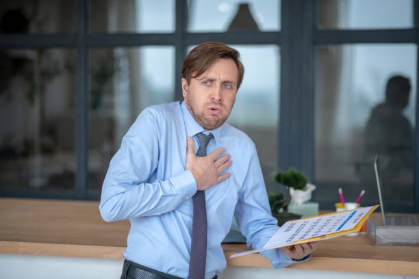 Blauäugiger junger Geschäftsmann hustet während der Arbeit im Büro – Foto