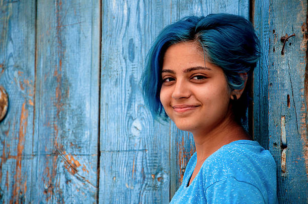 blue-haired young girl smiles stock photo