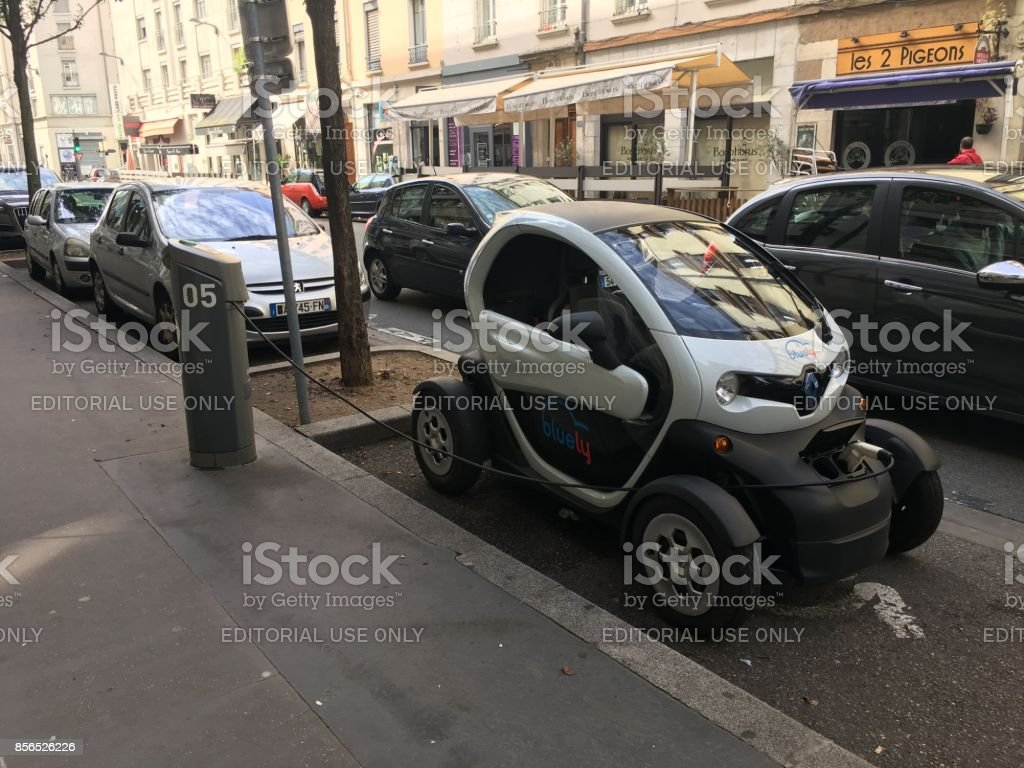 Bluely electric car sharing Renault Twizy plugged in the street in Grand Lyon stock photo