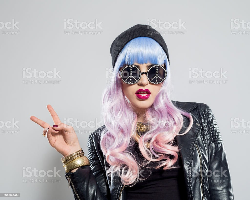 Blue-pink hair carefree girl showing peace sing stock photo