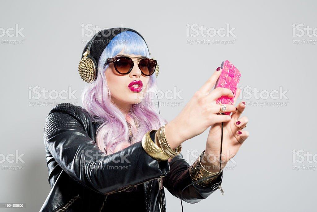 Blue-pink hair carefree girl wearing leather jacket taking selfie stock photo