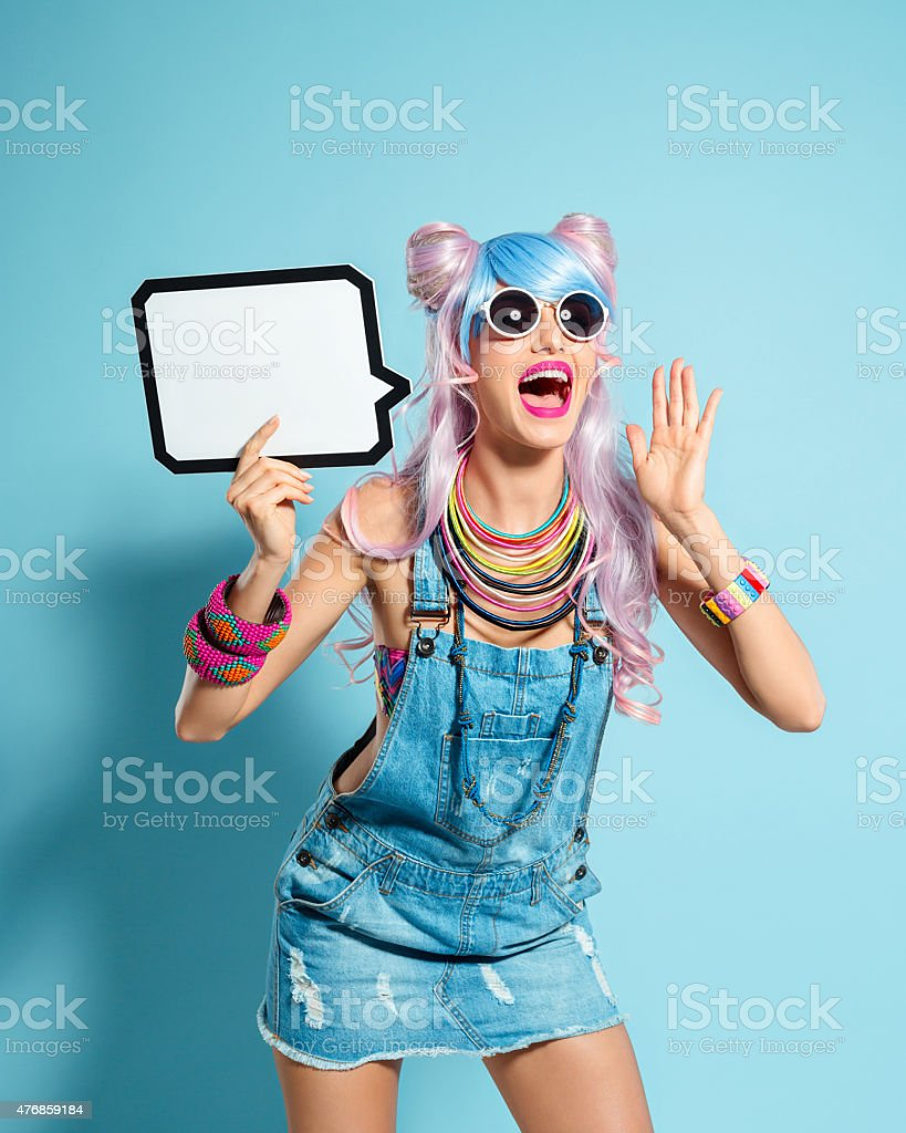 Blue-pink hair girl in funky manga outfit holding speech bubble Portrait of excited manga style blue-pink hair young woman wearing denim coveralls and sunglasses. Standing against blue background, holding a speech bubble in hand and screaming at the camera. Studio shot, one person. 2015 Stock Photo