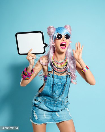 istock Blue-pink hair girl in funky manga outfit holding speech bubble 476859184