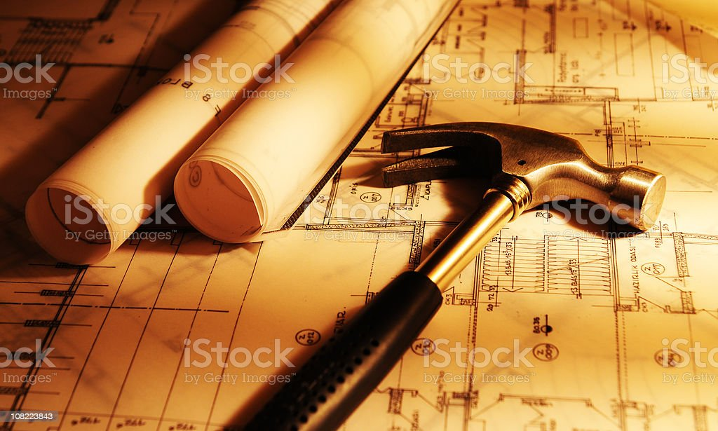 Blueprint and Hammer in Yellow Washed Light royalty-free stock photo