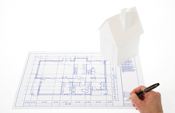 Blueprint approbation Architect signing a blueprint.  White carboard house over the drafting plan.  Hand holding a pen. White background. approbation stock pictures, royalty-free photos & images
