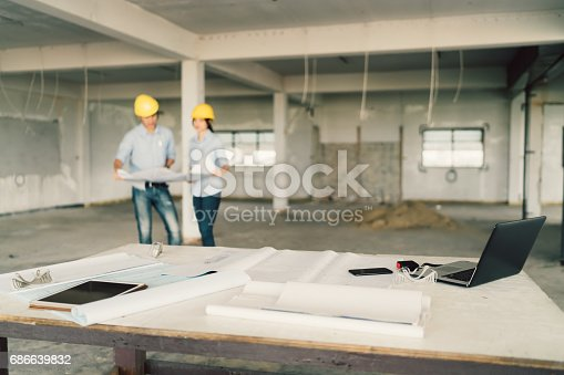 1129095769 istock photo Blueprint, laptop computer, and industrial tools at construction site with two engineers or architects working together in blur background. Industry, building architecture, or teamwork concept 686639832