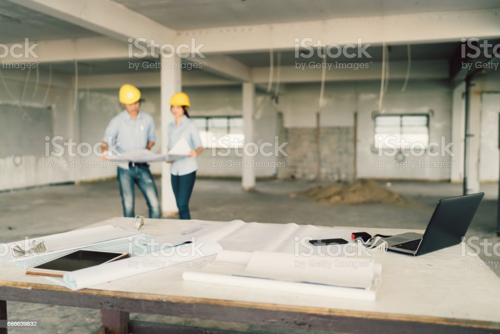 Blueprint, laptop computer, and industrial tools at construction site with two engineers or architects working together in blur background. Industry, building architecture, or teamwork concept – Foto