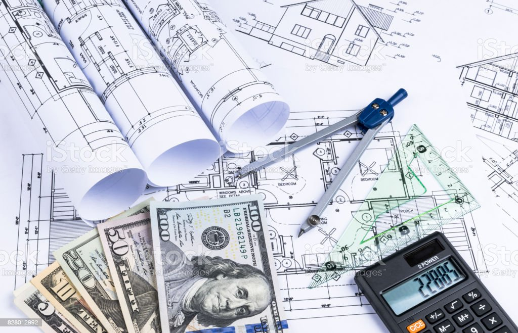 A blueprint of an architect with money, calculator. symbolic photo for financing and planning of a new house. Blueprints rolls and a drawing instruments on the worktable stock photo