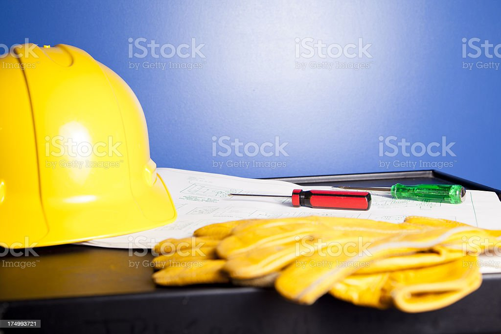 Blueprints with gloves and hardhat stock photo
