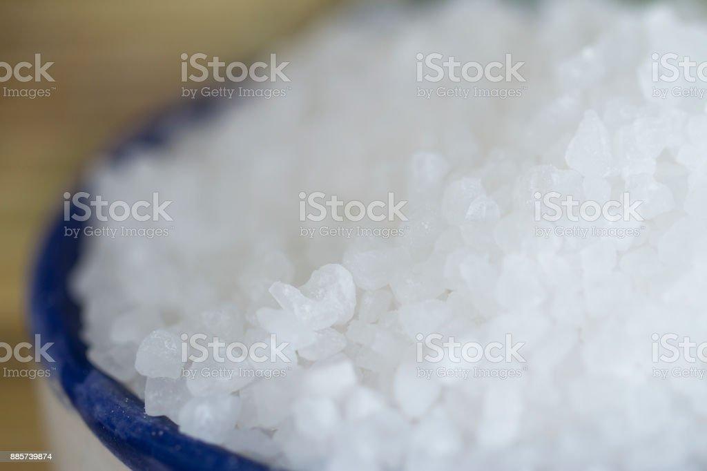 Blue-Rimmed Rustic Bowl Full of Coarse Sea Salt stock photo