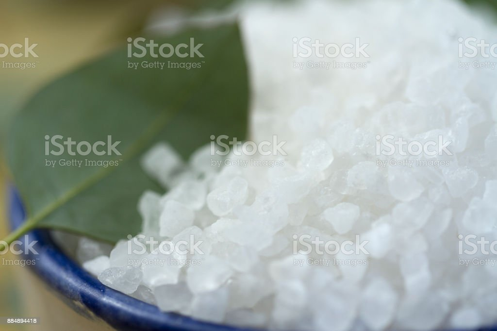 Blue-Rimmed Rustic Bowl Full of Sea Salt with Eucalyptus Leaves stock photo