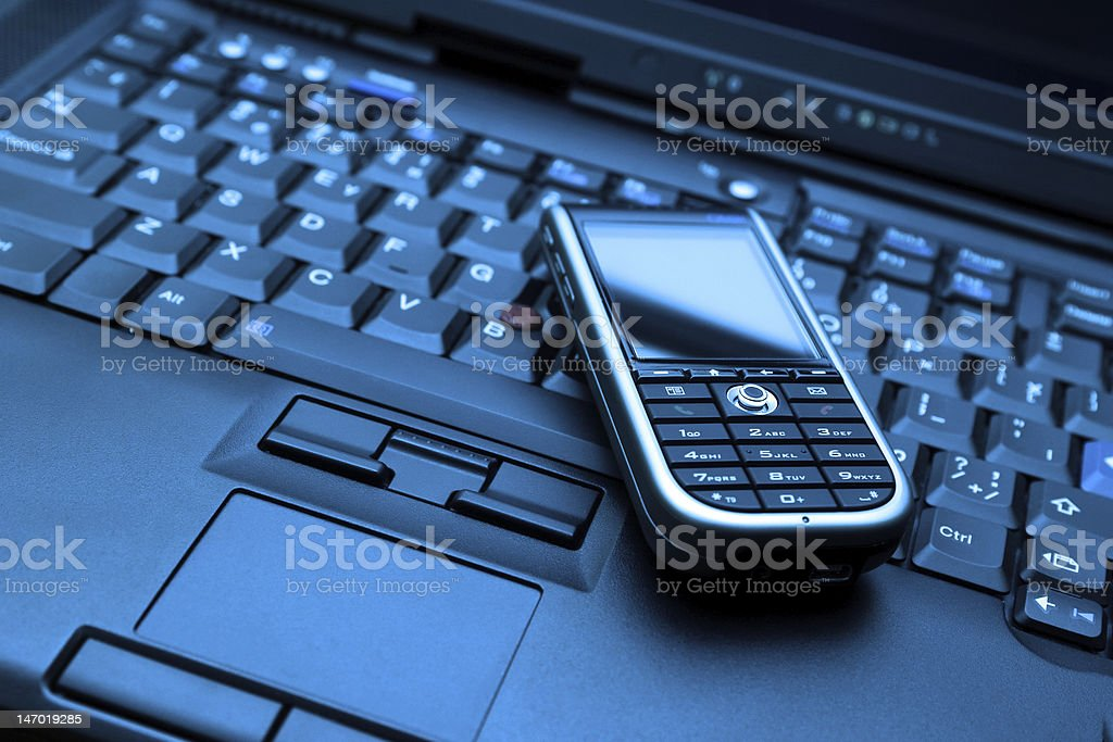 Blue-toned Connect. Laptop and smartphone royalty-free stock photo