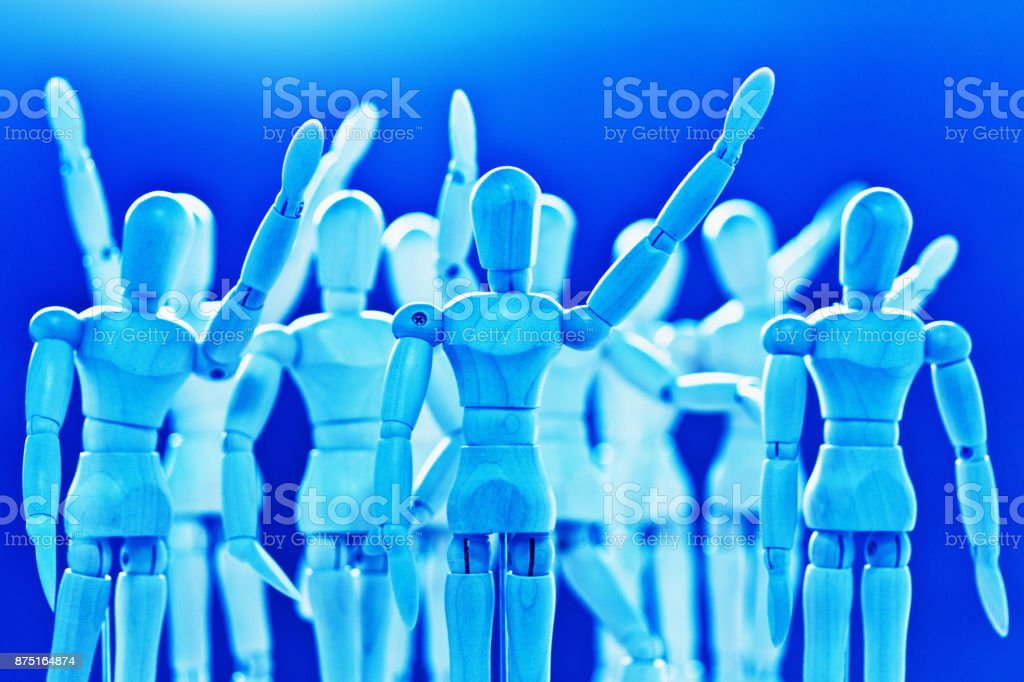 Blue-toned wooden puppets waving hello or goodbye stock photo