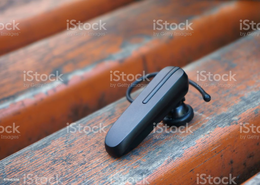 bluetooth headset lying on a bench royalty-free stock photo