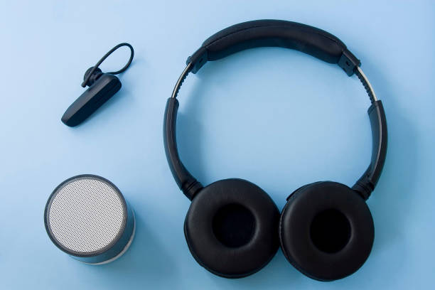 Bluetooth headset, speaker and earphone Bluetooth headset, speaker and earphone isolated on pastel blue desk. Flat lay. bluetooth stock pictures, royalty-free photos & images
