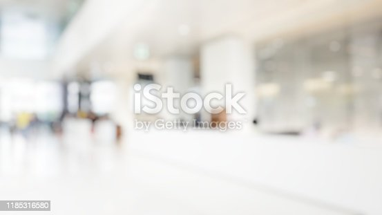 istock Blur abstract background of corridor in clean hospital. Blurred view of aisle in office with light floor. Blurry lobby and waiting area in hotel. Defocused empty area for event hall in shopping mall 1185316580