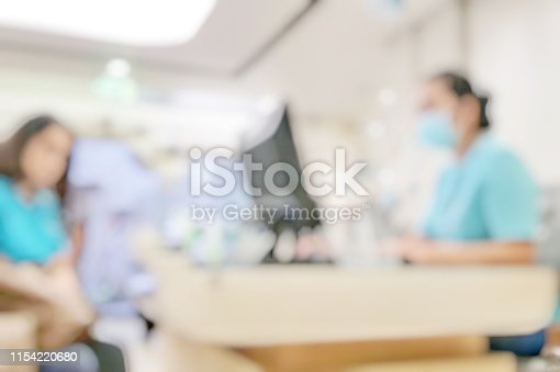 Blur abstract background of patients register at reception desk in hospital. Blurry nurse receptionists taking care new customers in medical clinic. Defocus reception area with worker. Healthcare concept.