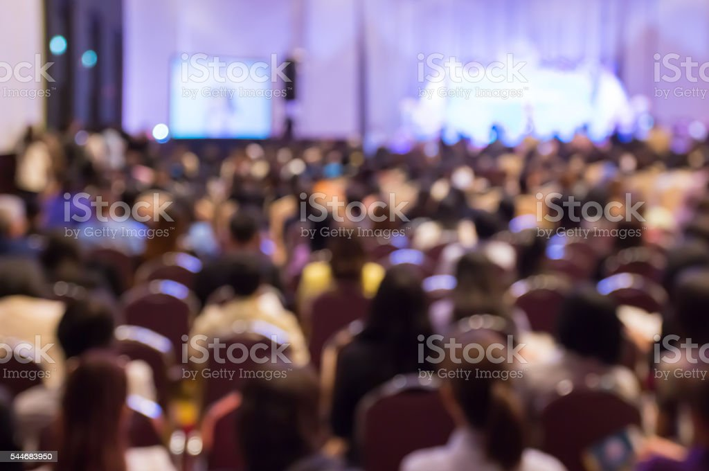 Blur audience sitting in hall or auditorium or classroom