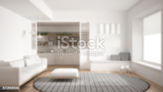 istock Blur background interior design, minimalist living room with sofa, big round carpet and kitchen in the background 820868930