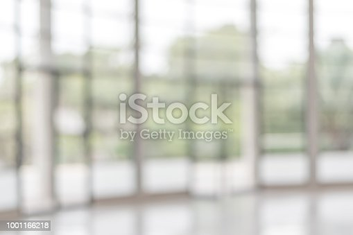 1009742300 istock photo Blur background interior view looking out toward to empty office lobby and entrance doors and glass curtain wall 1001166218