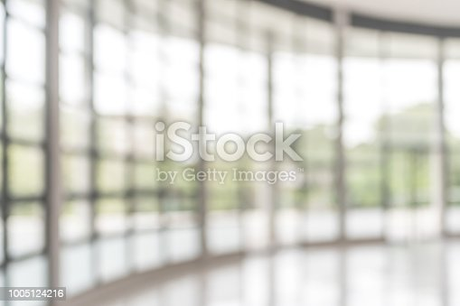 1009742300 istock photo Blur background interior view looking out toward to empty office lobby and entrance doors and glass curtain wall 1005124216