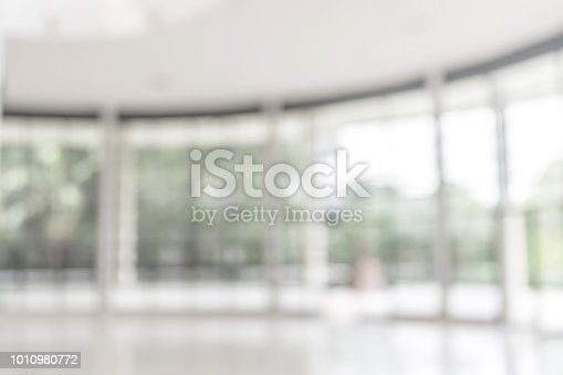 1009742300 istock photo Blur background interior view looking out toward to empty office lobby and entrance doors and glass curtain wall 1010980772