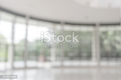1009742300 istock photo Blur background interior view looking out toward to empty office lobby and entrance doors and glass curtain wall 1014519484