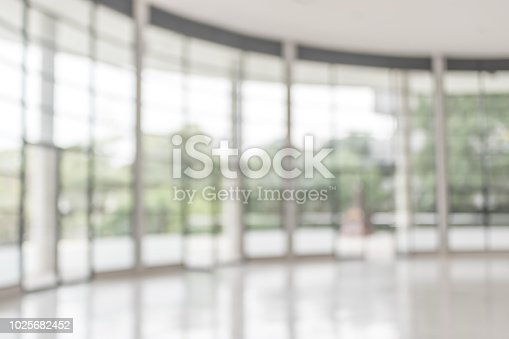 istock Blur background interior view looking out toward to empty office lobby and entrance doors and glass curtain wall 1025682452