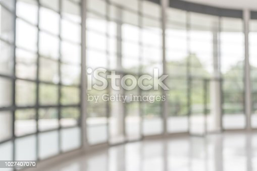 1009742300 istock photo Blur background interior view looking out toward to empty office lobby and entrance doors and glass curtain wall 1027407070