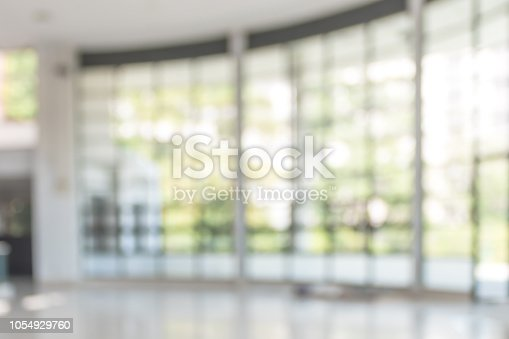1009742300 istock photo Blur background interior view looking out toward to empty office lobby and entrance doors and glass curtain wall 1054929760