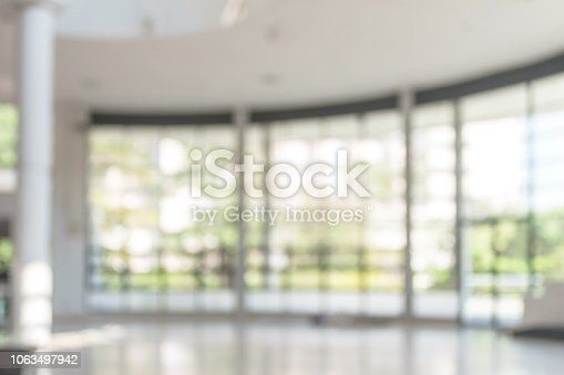 1009742300 istock photo Blur background interior view looking out toward to empty office lobby and entrance doors and glass curtain wall 1063497942