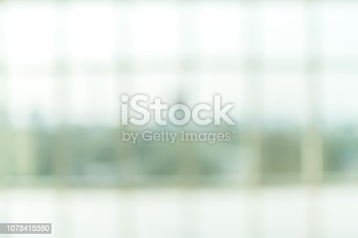 1009742300 istock photo Blur background interior view looking out toward to empty office lobby and entrance doors and glass curtain wall 1073415350