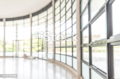 istock Blur background interior view looking out toward to empty office lobby and entrance doors and glass curtain wall 1075733266