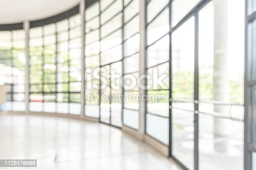 istock Blur background interior view looking out toward to empty office lobby and entrance doors and glass curtain wall 1125176569