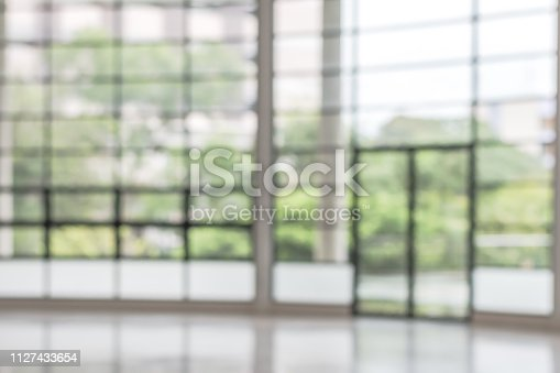 istock Blur background interior view looking out toward to empty office lobby and entrance doors and glass curtain wall 1127433654