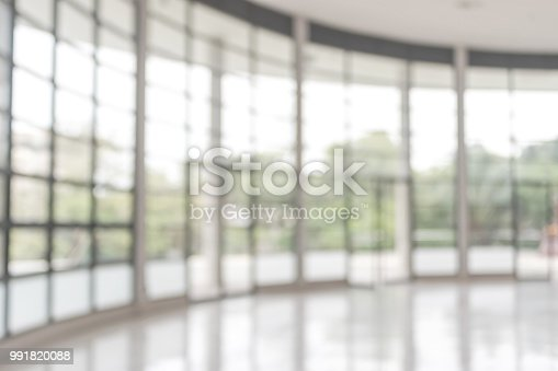 istock Blur background interior view looking out toward to empty office lobby and entrance doors and glass curtain wall 991820088