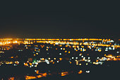 Panoramic image with burning candles and night blurred electric lights of a city beneath mountains. Selective focus on flames of candles. Concept of birthday, sixteen years old, place for greetings