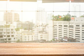 istock Blur background of white window glass and city view with empty of wood table. 1161733825