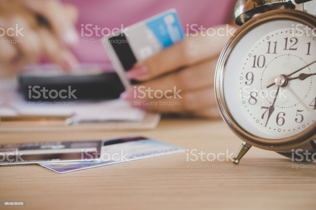 blur background of woman hand calculating  her expenses with some credit cards royalty-free stock photo