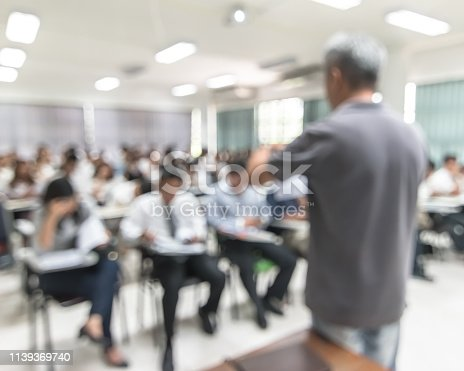 istock Blur background university students sitting in seminar lecture room with rear view teacher in front of class room 1139369740