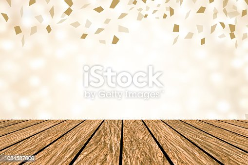 1034181324istockphoto blur beautiful soft gold color with spreading flying confetti and vinatge ood plank table background for design as show,advertisement,promote content,product on display concept 1084587606