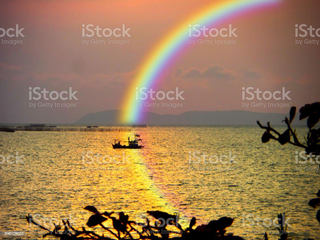 blur boat in sea sunset rainbow on sky and reflection rainbow on water