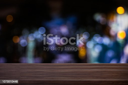 istock Blur cafe restaurant or coffee shop empty of dark wood table with blurred light gold bokeh abstract background for montage product display or design. 1073510448