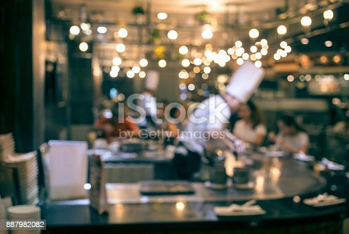 istock Blur chef cooking in restaurant with  customer 887982082