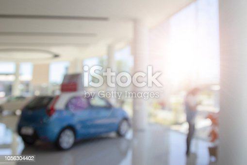 istock Blur colorful showroom a row of new cars parked at a car dealership stock customers to view and buy. Blurred in workplace abstract background of shallow depth of field for sale background use. 1056304402