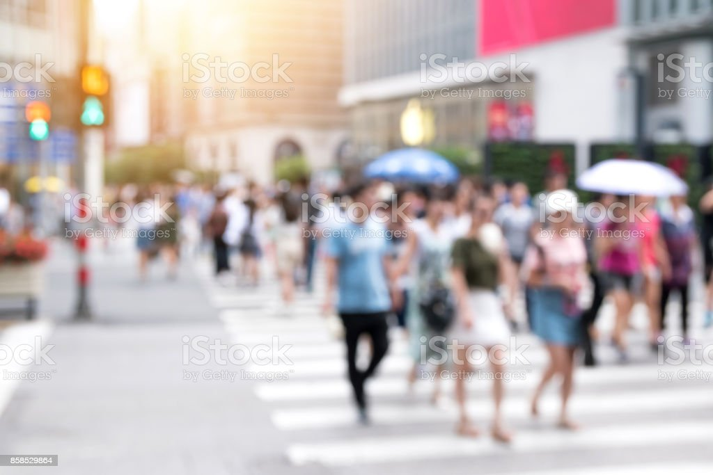 Blur crowd of people crossing down the street rush on the street in city life with flare light effect. The image is purposely made out of focus, no faces are recognizable. stock photo