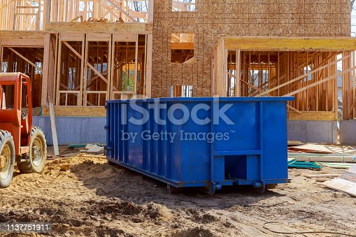 istock Blur dumpster, recycle waste and garbage bins near new construction site of appartment houses building 1137751911