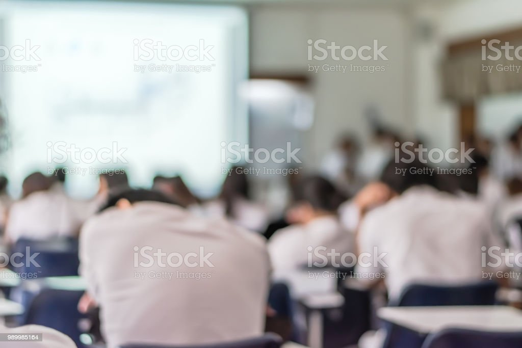 Blur education background lazy student audiences in lecture hall sleepy studying, feeling tired sleeping on school desk stock photo
